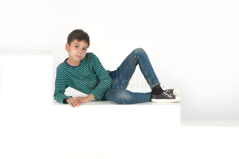 Der Junge sitzt auf weißen Schritten oder Kästen stockfotografie
