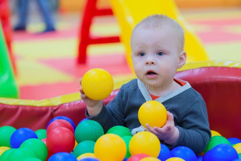 Der Junge sitzt in einem Stapel von Bällen in einem trockenen Pool und in den Spielen stockbild