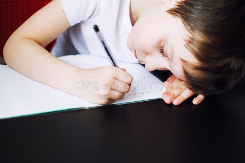 Der Junge sitzt am Tisch und schreibt in ein Notizbuch Kind sitzt und tut Hausarbeit stockbild