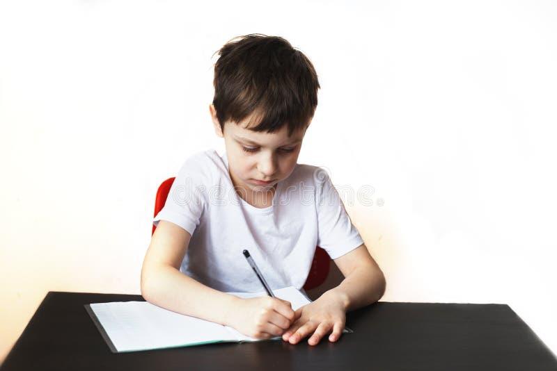Der Junge sitzt am Tisch und schreibt in ein Notizbuch stockfotos