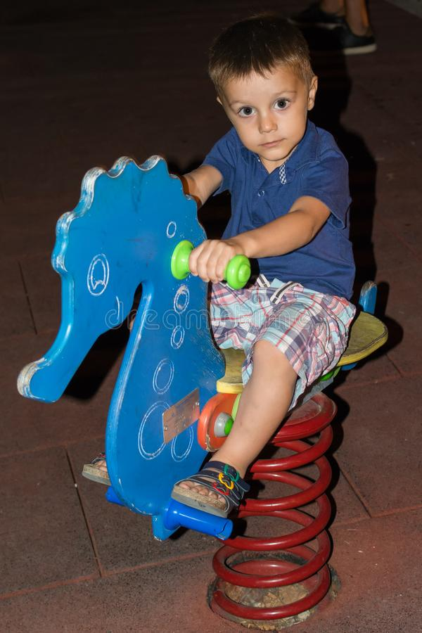 Der Junge spielt im Spielplatz nachts lizenzfreies stockfoto