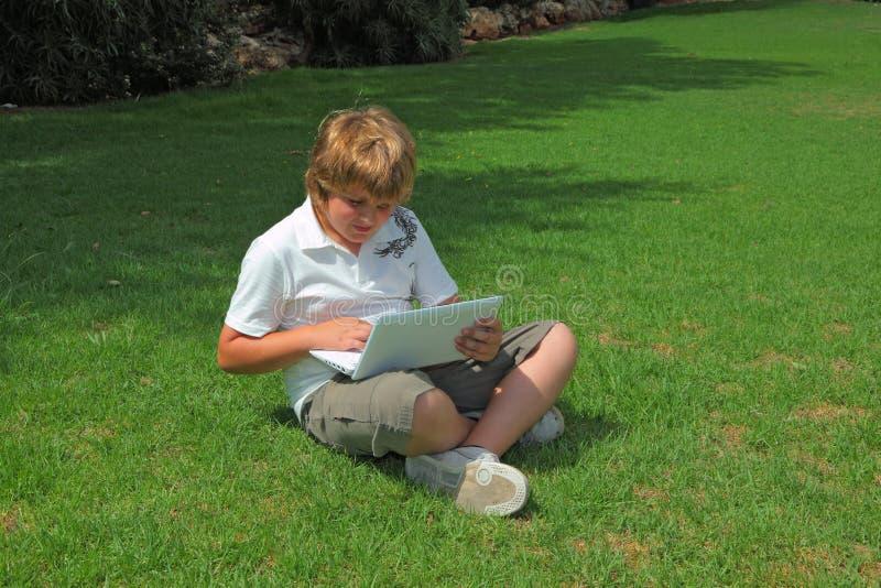 Der Junge spielte auf Laptop auf einem Rasen lizenzfreie stockfotos