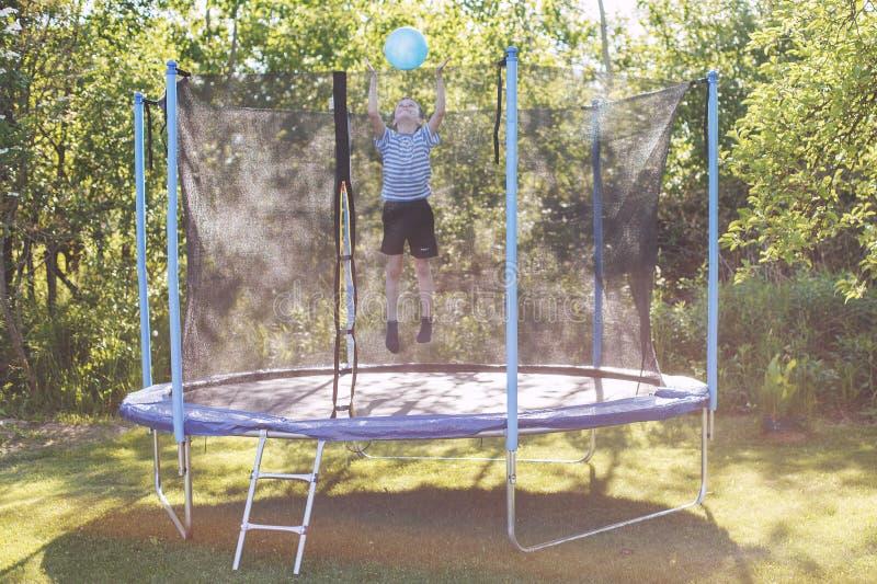 Der Junge springend auf Trampoline Kind, das mit einer Kugel spielt lizenzfreies stockfoto