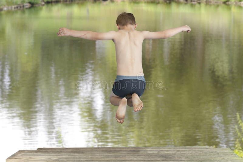 Der Junge springend in einen See stockfotos