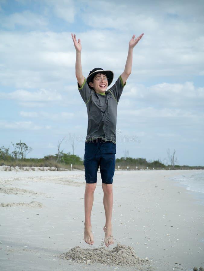 Der Junge springend für Freude auf dem Strand lizenzfreie stockbilder