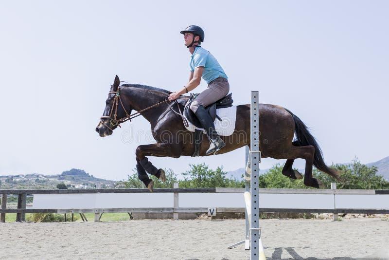 Der Junge springend mit Pferd lizenzfreie stockbilder
