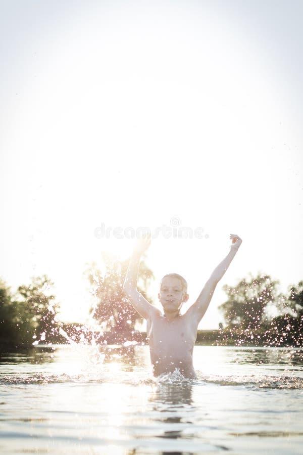 Der Junge springend oben in See stockfotos