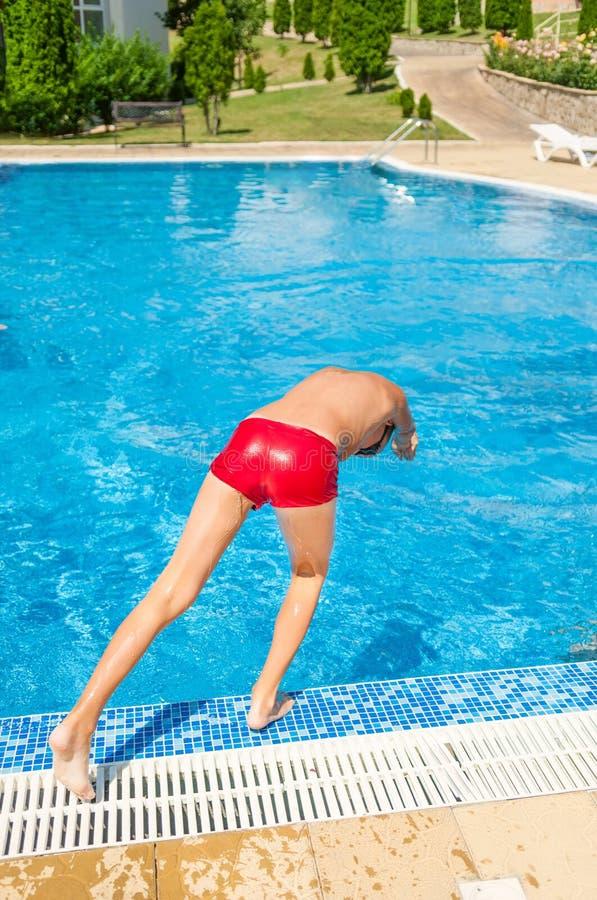 Der Junge springend in Swimmingpool lizenzfreie stockfotografie
