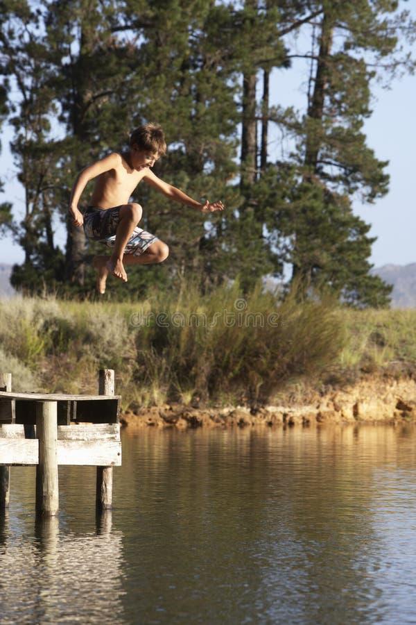 Der Junge springend von der Anlegestelle in See stockfoto