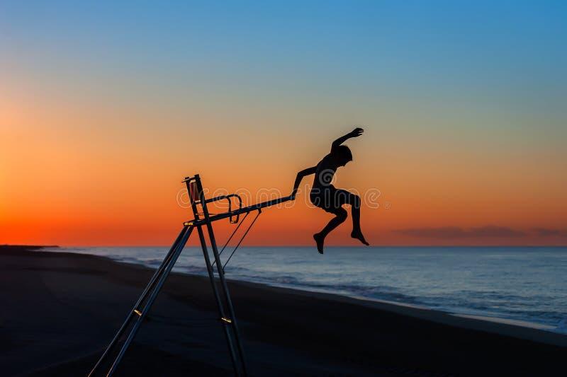 Der Junge springend weg von einem Leibwächterstuhl lizenzfreie stockfotos