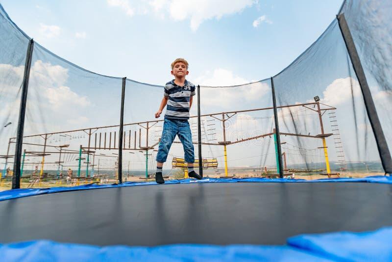 Der Junge springt auf eine Trampoline in einem Vergnügungspark und führt verschiedene Bremsungen durch lizenzfreie stockbilder