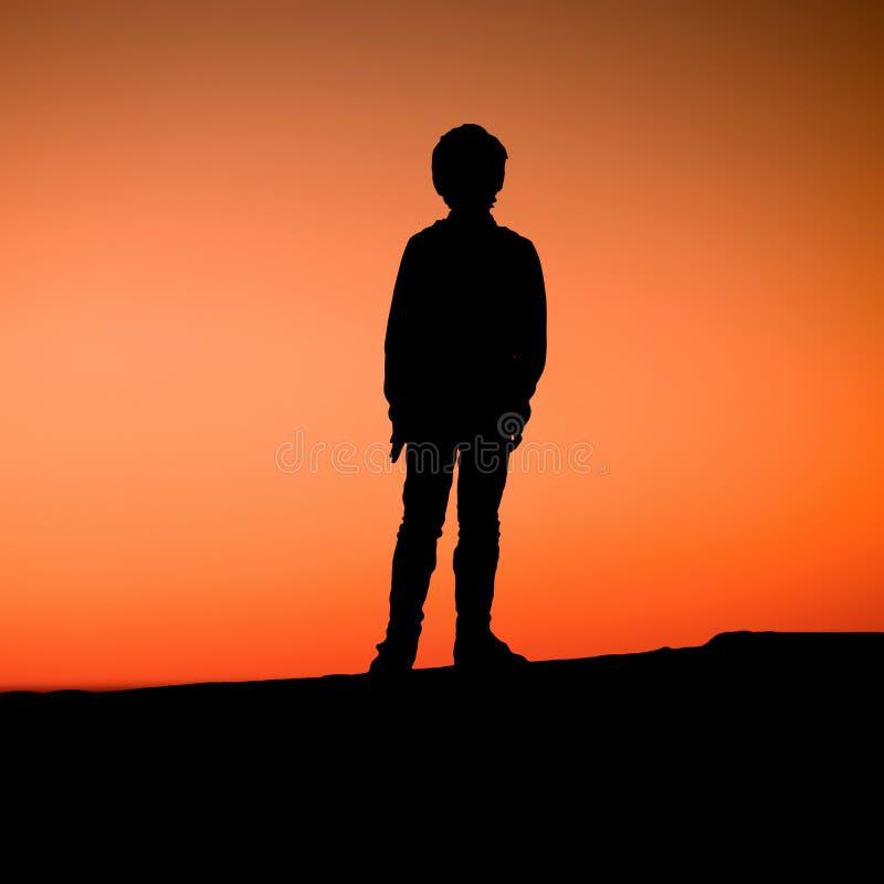 Der Junge steht auf Pier den Sonnenuntergang genießend lizenzfreie stockfotos