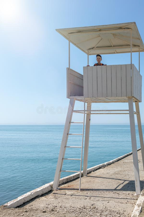Der Junge steht in einem Rettungsturm auf dem Strand lizenzfreie stockfotos