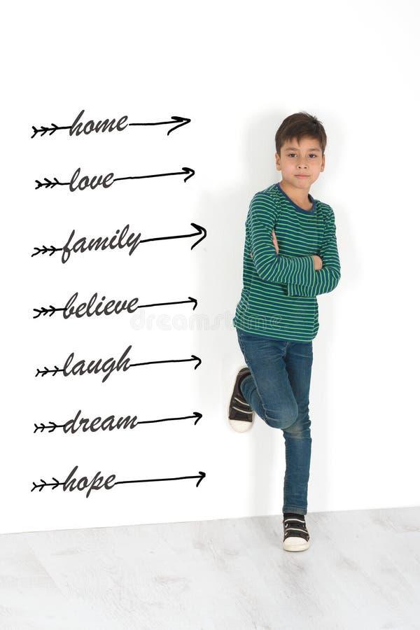 Der Junge steht an einer Wand und denkt an Lebenssinn lizenzfreies stockbild