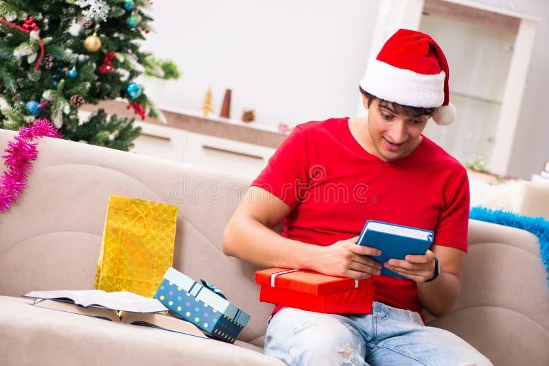 Der junge Student mit Buch am Weihnachtsabend stockfotografie