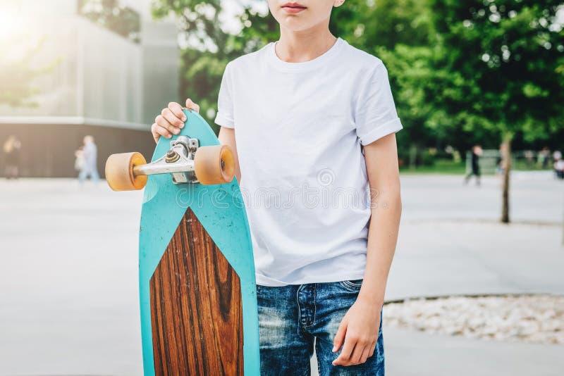 Der junge tausendjährige Junge, der im weißen T-Shirt gekleidet wird, ist Stände die im Freien Spott oben Raum für Logo, Text, Bi lizenzfreies stockfoto