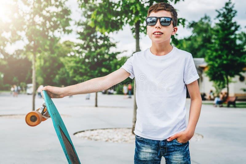 Der junge tausendjährige Junge, der im weißen T-Shirt gekleidet wird, ist Stände die im Freien Spott oben Raum für Logo, Text, Bi stockbild