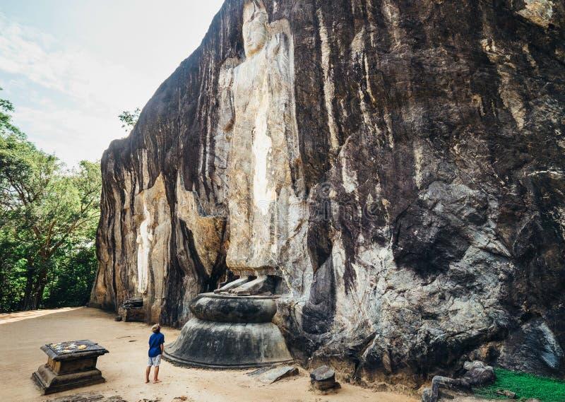 Der junge touristische Junge, der den Cca 1000 Jahre alt das größte der Stellung Buddha-Statuen genießt, ist 51 Fuß 16 m von Kopf lizenzfreie stockfotografie