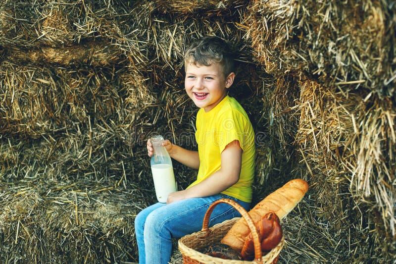 Der Junge trinkt Milch in der Natur stockbild