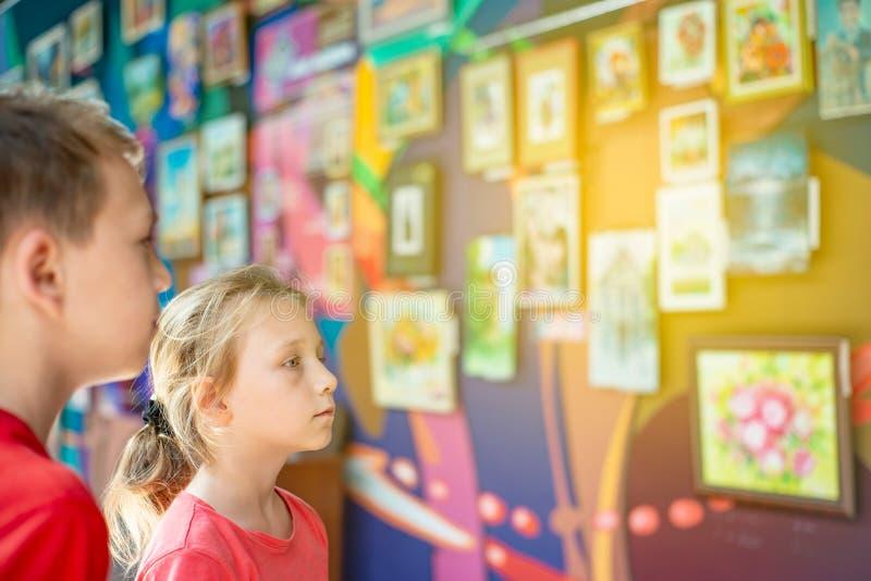 Der Junge und das Mädchen an der Ausstellung von Malereien und von Fotografien aufmerksam betrachtet die Malerei und genießt die  lizenzfreie stockbilder