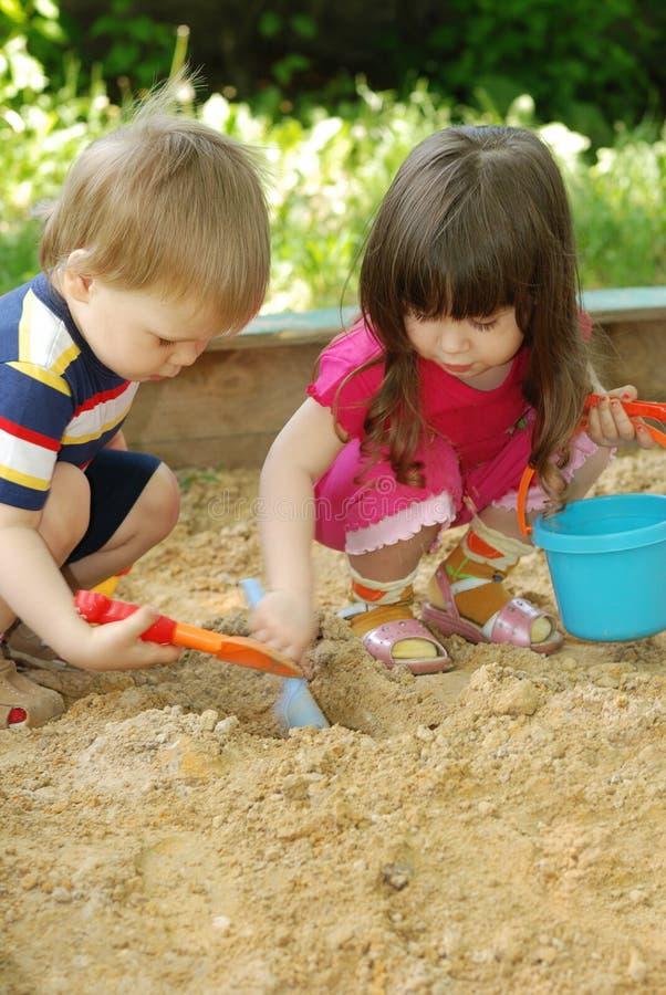 Der Junge und das Mädchen, die zu einem Sandkasten spielen stockfotografie