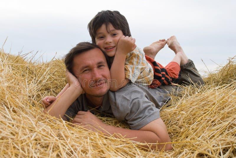 Der Junge und der Vater auf Heu lizenzfreie stockbilder