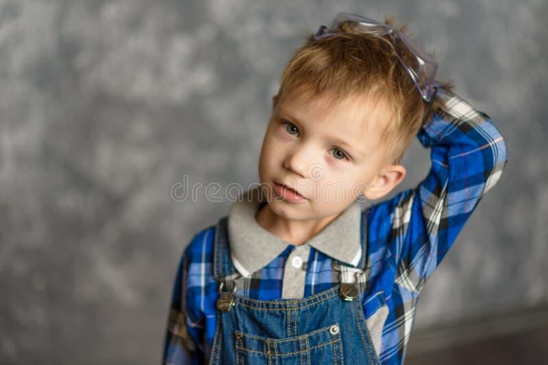 Der Junge verkratzt seinen Kopf lizenzfreie stockfotografie