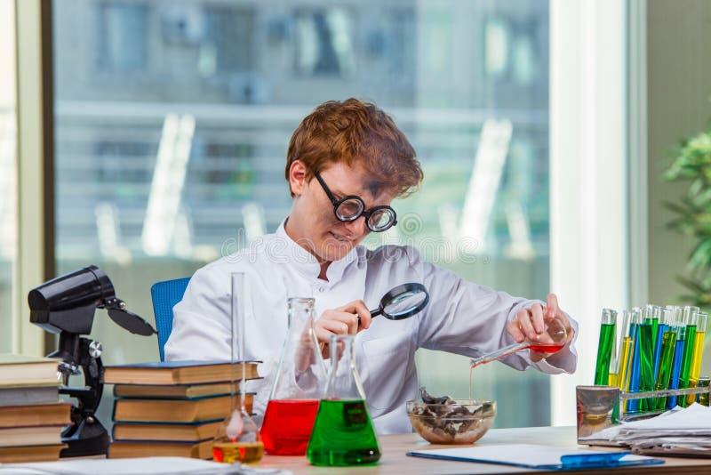 Der junge verrückte Chemiker, der im Labor arbeitet lizenzfreies stockbild