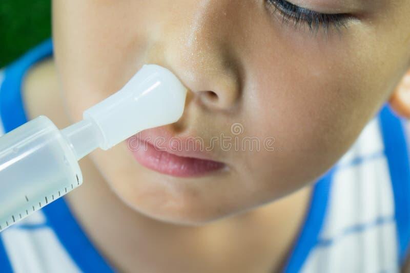 Der Junge wäscht Nase mit salzigem allein lizenzfreies stockbild