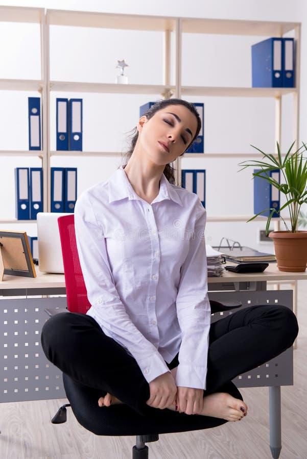 Der junge weibliche Angestellte, der Übungen im Büro tut lizenzfreies stockfoto