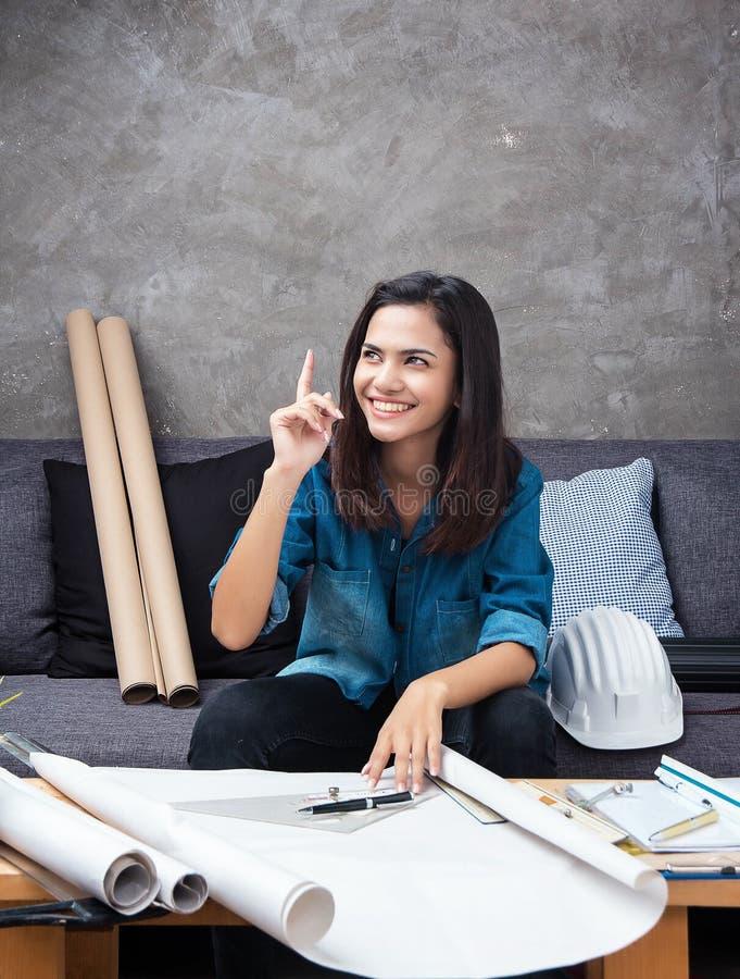 Der junge weibliche Architekt, der an Projekt arbeitet, ist sie Erhöhungsrechte hand oben und Punktfinger in der Luft, mit Lächel stockbilder