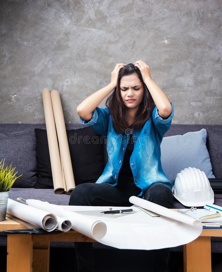 Der junge weibliche Architekt, der an Projekt, mit ernstem Gefühl arbeitet lizenzfreie stockfotos