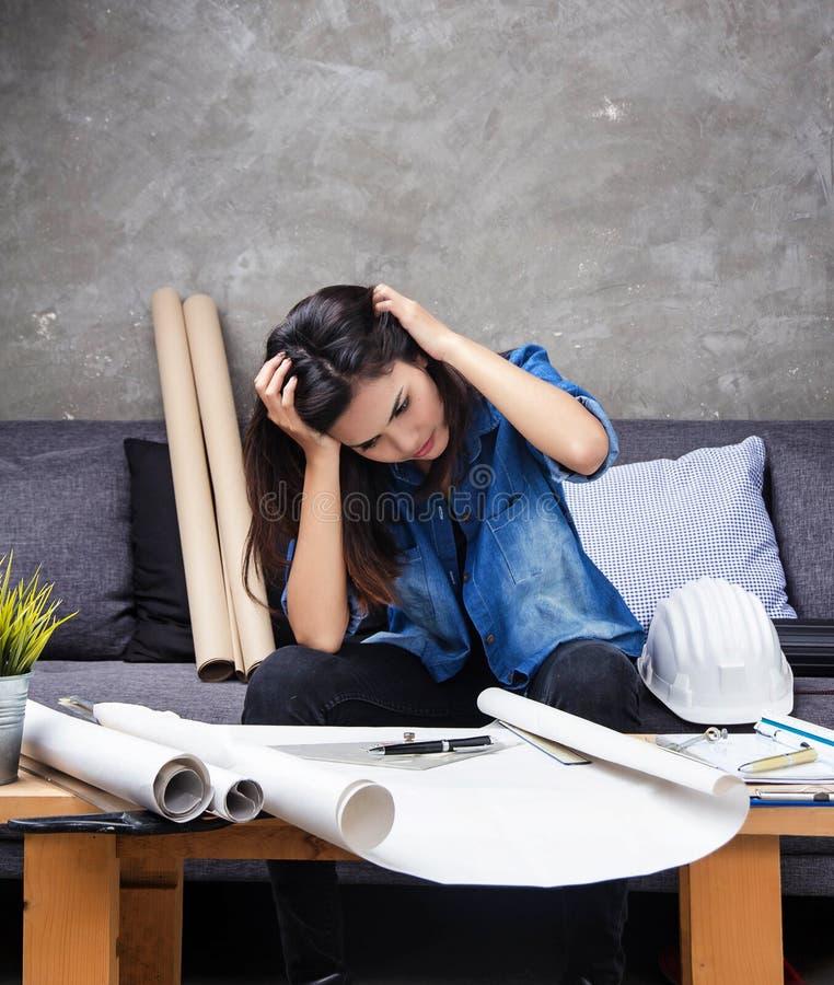 Der junge weibliche Architekt, der an Projekt, mit ernstem Gefühl arbeitet, ist sie Erhöhung ihr Handnotenkopf und denkt an Schre stockfotografie