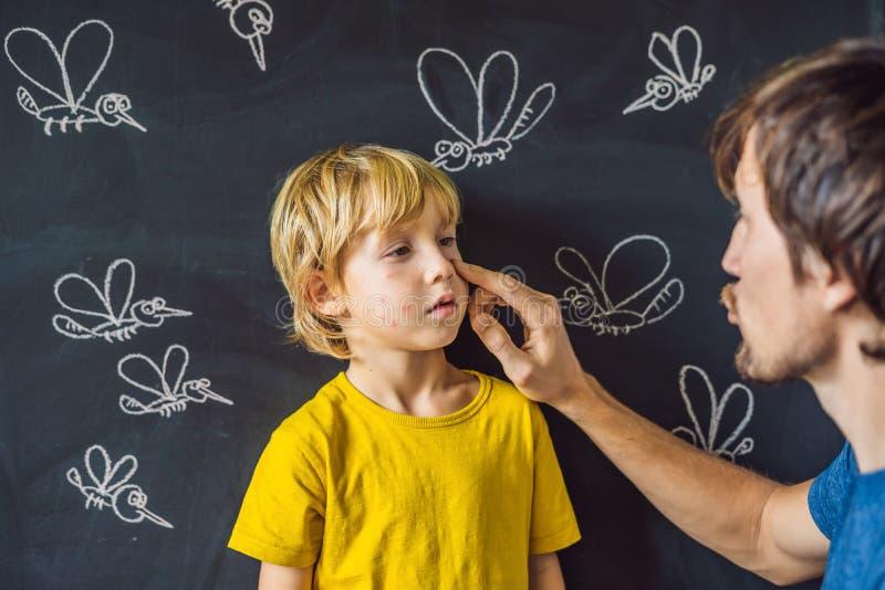 Der Junge wird durch Moskitos auf einem dunklen Hintergrund gebissen Vati schmiert seine Bisssalbe Auf der Tafel mit der Kreide g lizenzfreie stockfotos