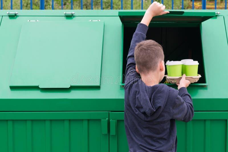 Der Junge wirft heraus vier Gläser von unterhalb der Getränke im Abfalleimer, hintere Ansicht, über das links dort ist ein Platz  stockfoto