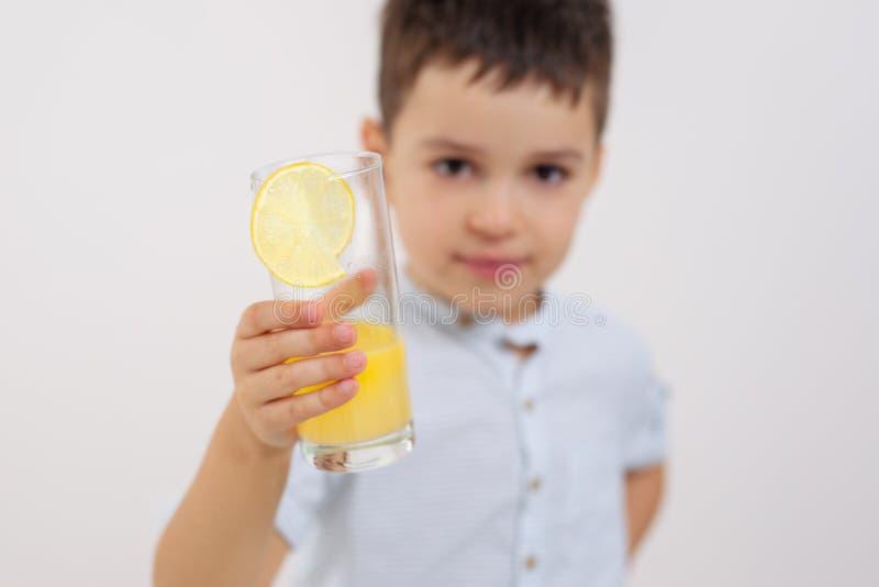 Der Junge zeigt ein Glas mit Limonade lizenzfreies stockfoto