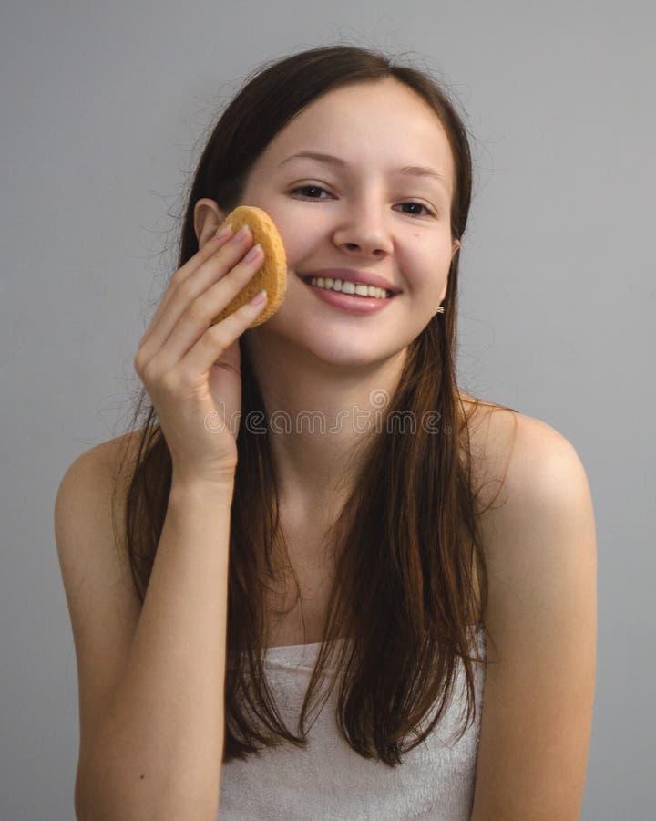 Der junges Mädchen Brunette wäscht ihr Gesicht stockfotos