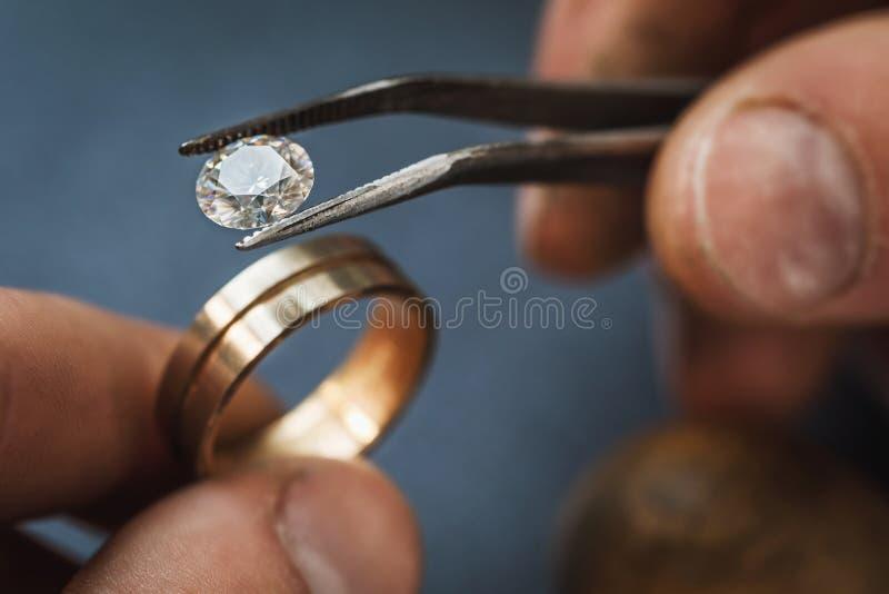 Der Juwelier schätzt den Edelstein zu einem Goldfreien raum für einen zukünftigen Ring lizenzfreies stockfoto