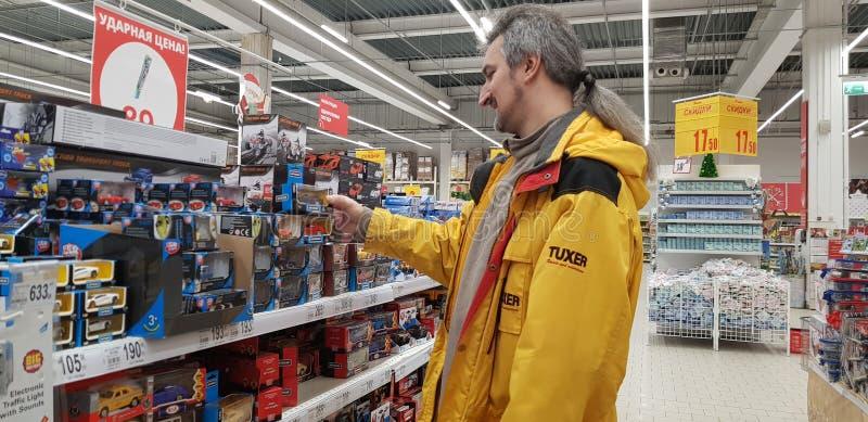 Der Käufer wählt die Spielwaren der Kinder, Automodelle im Supermarkt lizenzfreie stockfotos