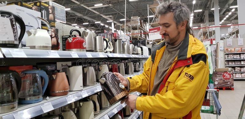 Der Käufer wählt einen Kessel im Speicher lizenzfreies stockfoto