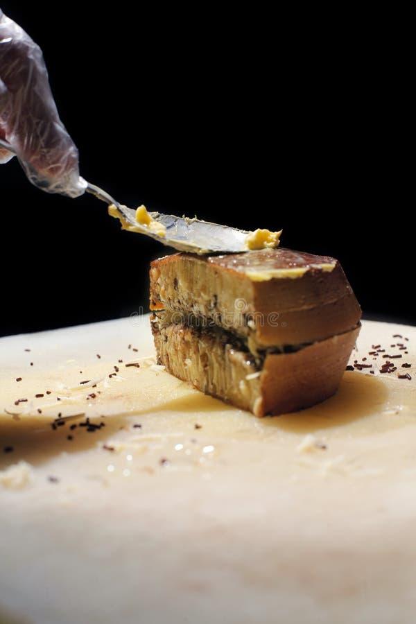 Der Küchenchef schmiert ein Stück süßen Martabak mit Butter mit einem Löffel stockfotografie
