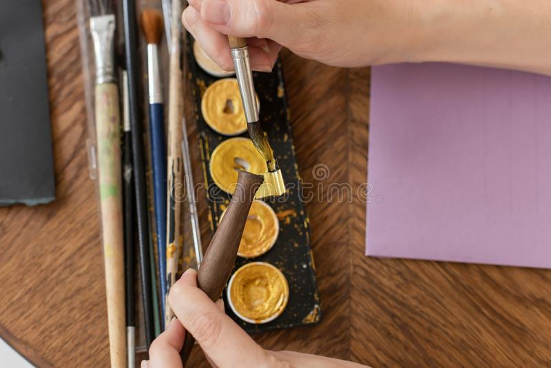 Der Künstler bereitet vor sich zu arbeiten Wendet Farbe an der Bürste an Nahaufnahme Die Atmosphäre der kreativen Werkstatt lizenzfreies stockfoto
