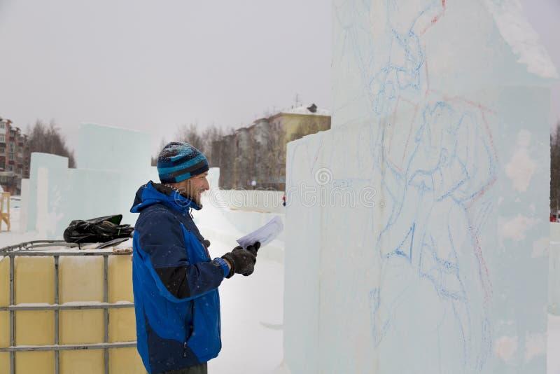 Der Künstler zeichnet auf den Eisblock lizenzfreies stockfoto