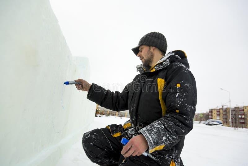 Der Künstler zeichnet auf den Eisblock stockbilder