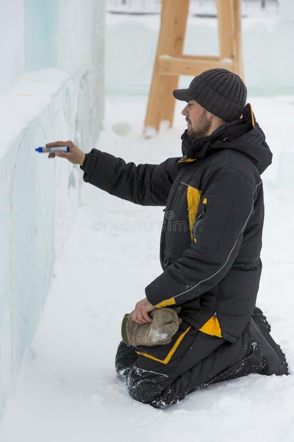 Der Künstler zeichnet auf den Eisblock stockfotos