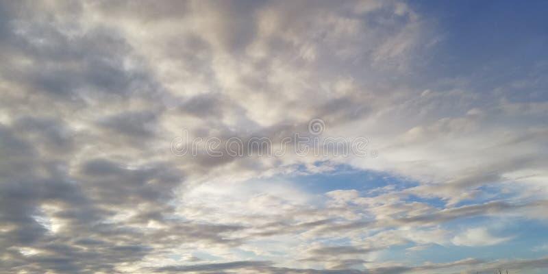Der Kampf des Licht und Dunkelheit Helle weiße Wolken und dunkle Wolken im blauen Himmel Interessanter ungewöhnlicher Hintergrund lizenzfreie stockbilder