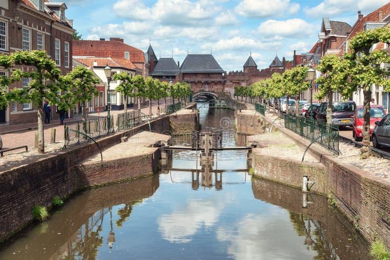 Der Kanal Eem mit im Hintergrund das mittelalterliche Tor das Koppelpoort in der Stadt von Amersfoort in den Niederlanden lizenzfreie stockfotografie