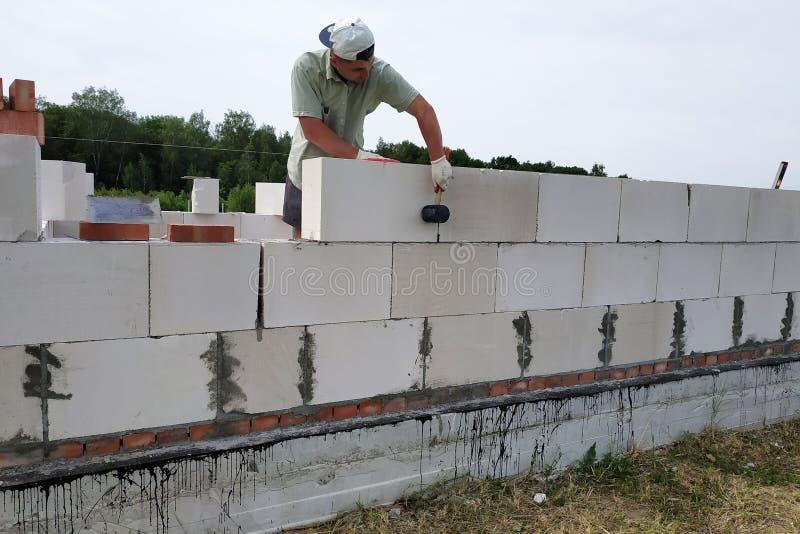 Der Kapitän führt Bauarbeiten, d. h. die Verlegung einer Wand mit Werkzeugen und Klebemörtel, im Hintergrund der die stockbild