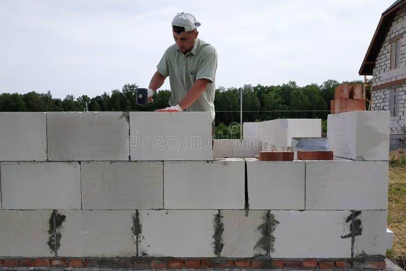 Der Kapitän führt Bauarbeiten, d. h. die Verlegung einer Wand mit Werkzeugen und Klebemörtel, im Hintergrund der die lizenzfreie stockfotos