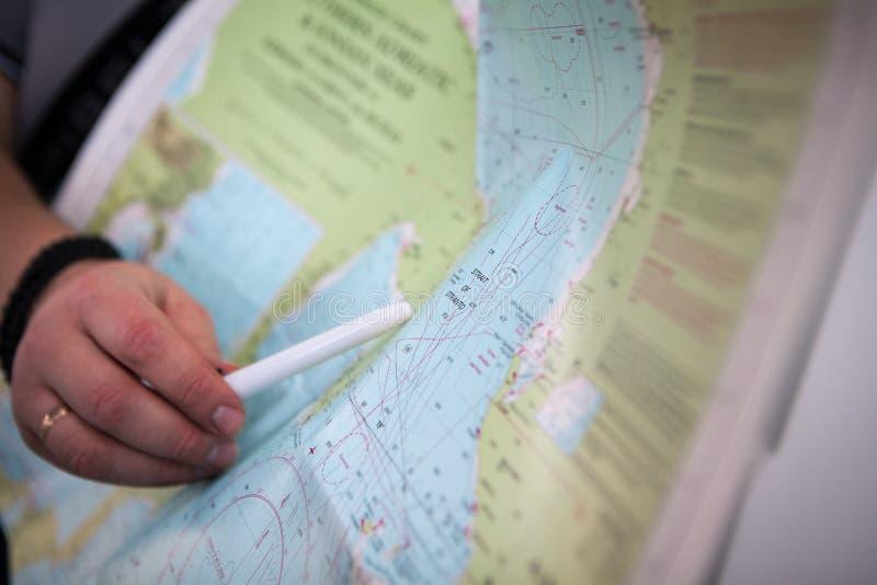 Der Kapitän zeigt den Plan der Straßenüberfahrt auf der Karte stockfoto